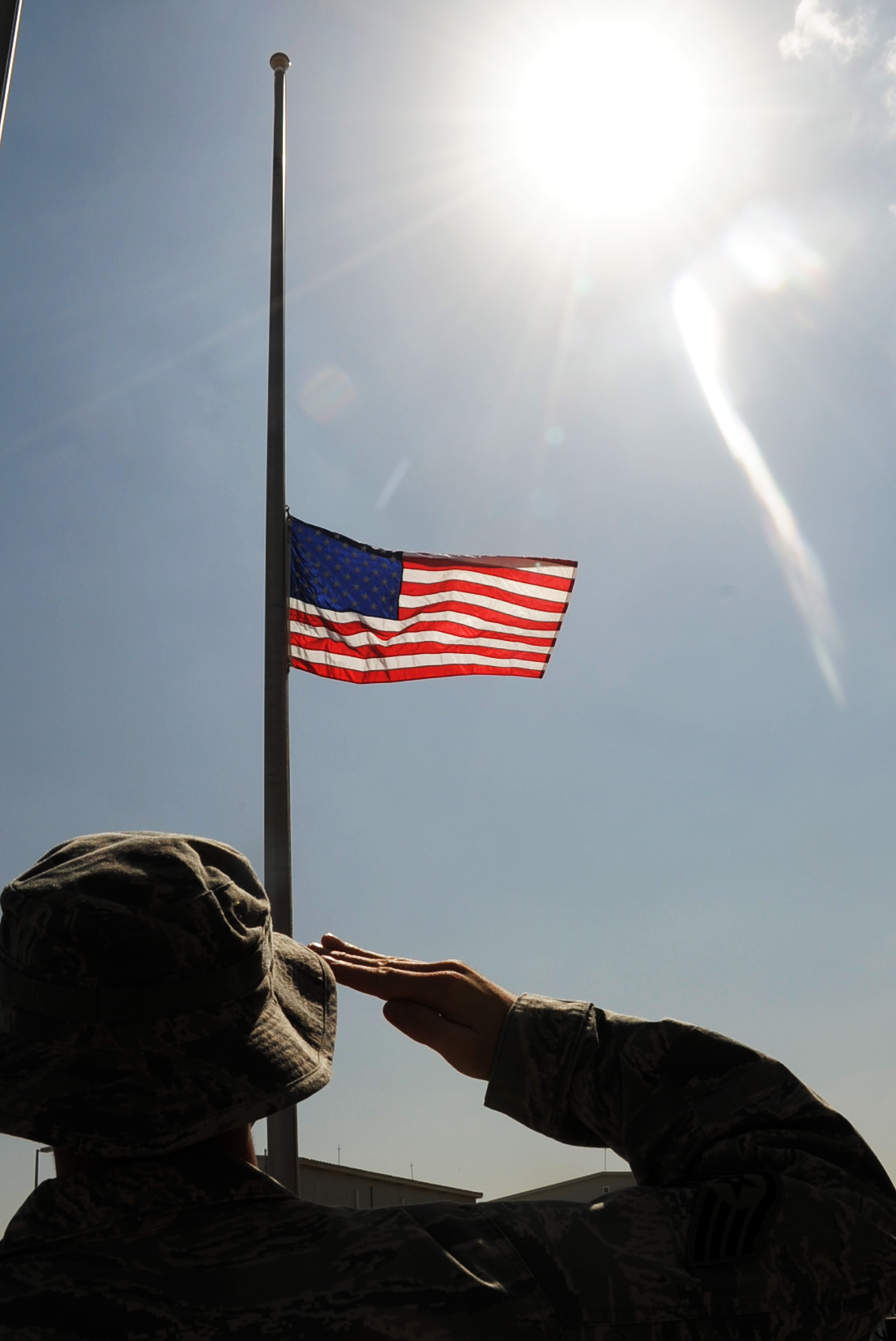 An Airman assigned to the 380th Air Expeditionary Wing at a non-disclosed base in Southwest Asia salutes the American flag, Feb. 9, that is flying at half-mast in honor of U.S. Representive John Murtha of Pennsylvania who died, Feb. 8. Representative Murtha was a military veteran who earned the Bronze Star and two Purple Hearts during the Vietnam War. Military installations around the world flew the flag at half-mast Feb. 9 in honor of Representative Murtha by declaration from President Barack Obama.