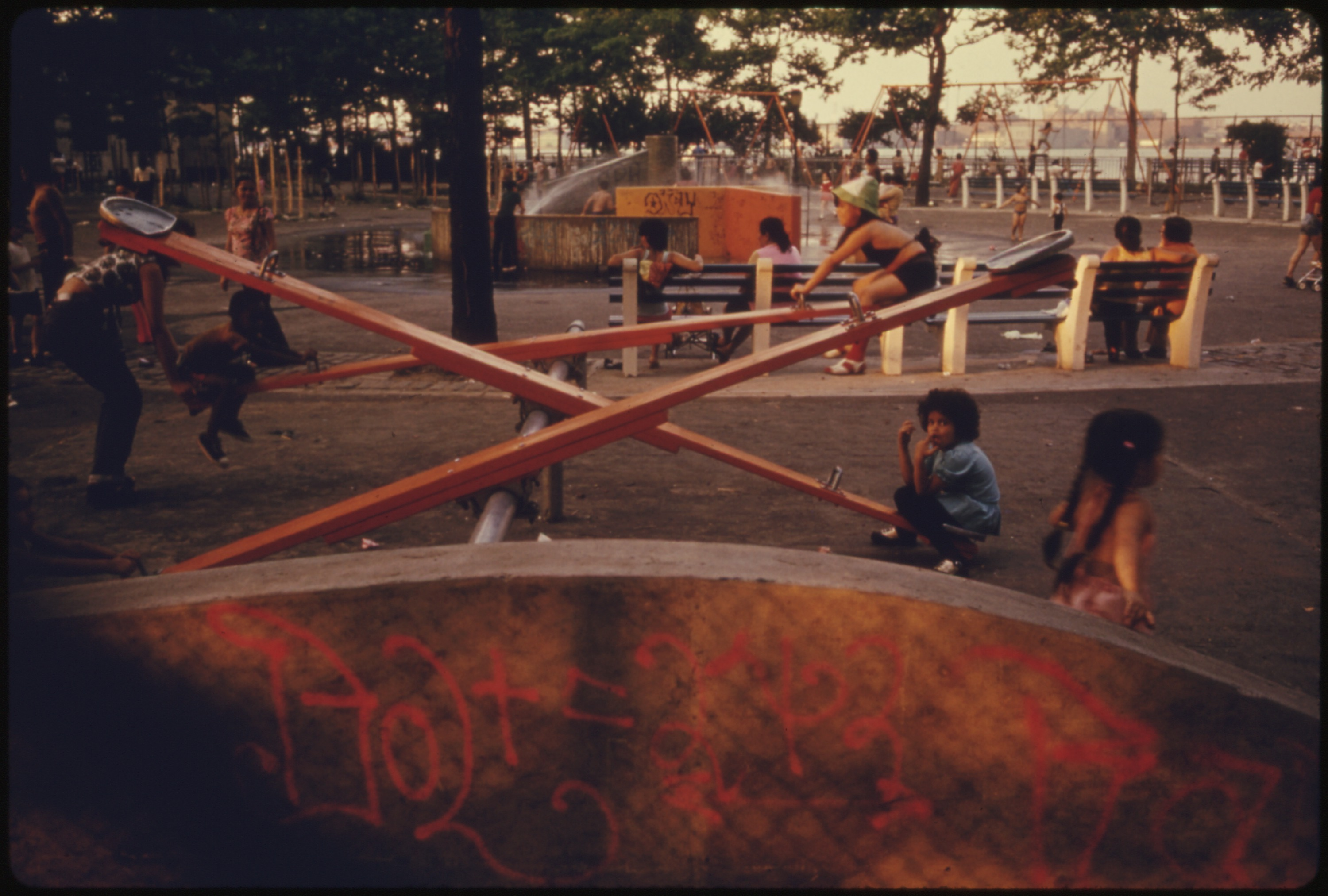 KIDS_ENJOYING_PLAYGROUND_EQUIPMENT_IN_EAST_RIVER_PARK_IN_MANHATTAN,_NEW_YORK_CITY._THE_INNER_CITY_TODAY_IS_AN..._-_NARA_-_555946